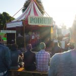 A group enjoys music in the park under a circus tent