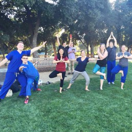 Group poses for a photo while performing yoga poses