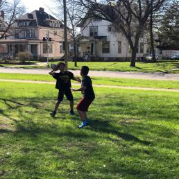 Two young boys toss a football in the grass