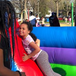 Two girls interact on a bouncing obstacle course