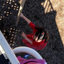 A girl plays in a red dress