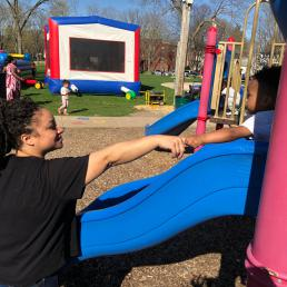 A mother reaches for her son as he plays on the slide