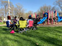 Group of park-goers sit in lawn chairs near park playground equipment.