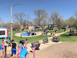A large group of community members gather in the park.