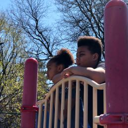 Two kids peer over the park equipment and observe park activity