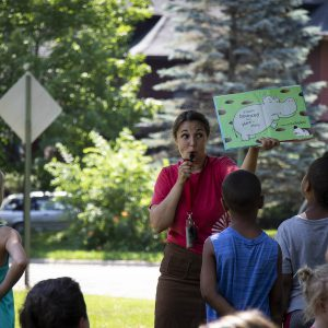A group of children surround a librarian reading a book in Redmond Park