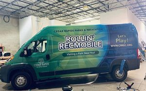 "A van with lettering printed on its side, ""Let's Play - Rollin' Recmobile"""